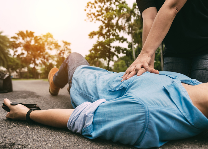 Man providing emergency first aid to a casualty on the street
